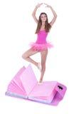 Ballerina making a pirouette. Young ballerina making a pirouette and dancing on top of a pink book Stock Photos
