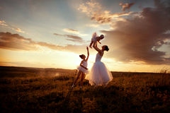 Ballerina mother and daughters. Mom teaches daughters ballet in a field at sunset Royalty Free Stock Photos