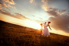 Ballerina mother and daughters. Mom teaches daughters ballet in a field at sunset Royalty Free Stock Photo