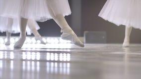 ballerina Närbilden av en flicka` s lägger benen på ryggen i vita balettskor under balettutbildning Beståndsdel av den klassiska  arkivfilmer