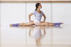 Ballerina på golv i kluven position Fotografering för Bildbyråer