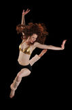 Ballerina performing. Wearing a dress against a black background Stock Image