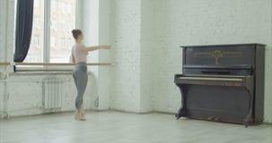 Ballerina performing battement tendu jete exercise. Graceful elegant ballerina performing battement tendu jete exercise during rehearsal in ballet studio stock video