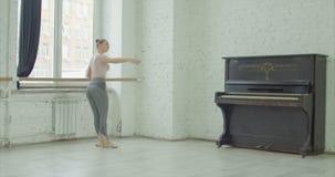 Ballerina performing rond de jamb par terre exercise. Graceful elegant ballerina performing rond de jamb par terre exercise during rehearsal in ballet studio stock video