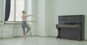 Ballerina performing sur le cou de pied exercise. Graceful elegant ballerina performing sur le cou de pied exercise during rehearsal in ballet studio. Charming stock video footage
