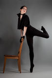 Ballerina performs exercises near the chair Royalty Free Stock Photos