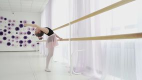 Ballerina piccola che allunga fuori vicino alla sbarra di balletto nello studio leggero sul fondo del wingow archivi video