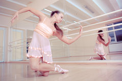 Ballerina in pink dress аgainst studio Royalty Free Stock Photography