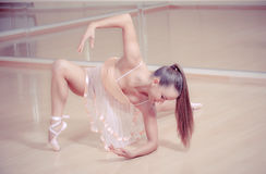 Ballerina in pink dress аgainst studio Royalty Free Stock Image