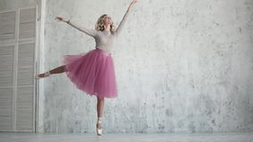 Ballet dancer in a pink tutu and pointe shoes. beautiful young ballerina at a rehearsal. lightness and grace of the. Ballerina in a pink tutu and pointe shoes stock video footage