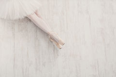 Ballerina in pointe ballet shoes, graceful legs with copy space. Ballet background. Closeup of young ballerina legs in pointe shoes on white wooden floor, top Royalty Free Stock Photos