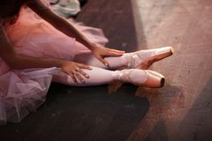 Ballerina in pointe shoes behind the scenes. Ballerina in pointe shoes, sitting on the floor behind the scenes in the intermission of the ballet royalty free stock image