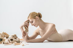Ballerina with pointe shoes. Cute ballerina with closed eyes lies on the light floor in the studio. She holds a pointe shoe in her hands and leans it to the royalty free stock image
