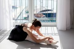 Ballerina in pointe shoes is doing exercises and dance workout in ballet class room Girl is sitting on floor near window