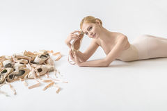Ballerina with pointe shoes. Joyful ballerina lies on the light floor in the studio. She holds a pointe shoe in her hands and leans it to the forehead. On the royalty free stock photos