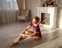 Ballerina in pointe shoes makes ballet leg stretching, morning sunshine. Portrait of a professional ballet dancer sitting on the wooden floor Stock Photo