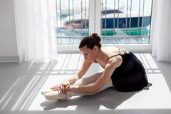 Ballerina in pointe shoes is sitting on floor near big window with view of sea and yachts. Girl is doing exercises