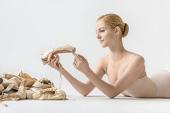 Ballerina with pointe shoes. Smiling ballerina lies on the light floor in the studio. She holds a pointe shoe in her hands and looks on it. On the left side royalty free stock photography