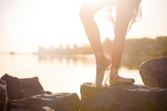 Talented ballerina with pointe shoes on the beach at sunset royalty free stock images