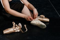 Ballet-dancer ties up pointe shoes. no face. back. girl royalty free stock photos