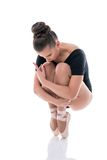 Ballerina on pointes, clutching her knees to chest Stock Images