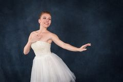 The ballerina in pointes and a white dress dances on a dark back. Ground in studio, half-length Royalty Free Stock Image