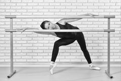 Ballerina posing in barre frame at ballet studio,full length portrait of beautiful woman dancer looking at camera. Blac