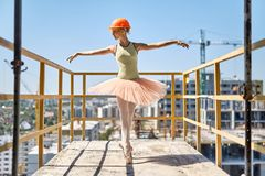 Ballerina posing at concrete balcony. Joyful ballerina stands on the toes on the concrete balcony of the unfinished building on the cityscape background. She stock images