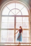Ballerina is posing in front of a large window Royalty Free Stock Photos