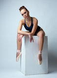 Ballerina posing with her legs dangling from cube Royalty Free Stock Photos