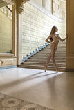 Ballerina posing in interior. Attractive ballerina stands on pointes next to the stairway in the luxury interior. She wears a beige leotard and ballet shoes Royalty Free Stock Image