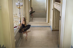 Ballerina posing in interior. Charming ballerina in a black tutu with colorful rhinestones stands next to the stairway in the luxury interior. Her left leg is in Royalty Free Stock Image