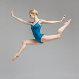 Ballerina posing in jump. Charming ballerina posing in the jump on the gray background in the studio. She wears a blue leotard. Her legs and arms stretched to royalty free stock image