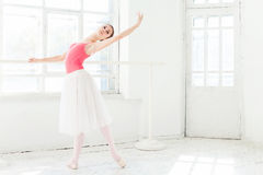 Ballerina posing in pointe shoes at white wooden pavilion Royalty Free Stock Photography