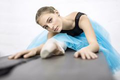 Ballerina posing in studio. Charming ballerina presses her torso to the leg on the wooden table on the white wall background in the studio. She wears a black Stock Photography