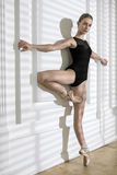 Ballerina posing in studio. Cute ballerina leans with stretched arms on the white wall while stands on the left toe. She wears black leotard with pointe shoes Stock Photos