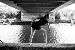 Ballerina posing under the bridge. A beautiful young ballerina is posing underneath a bridge with the river behind her. Lots of beautiful leading lines for fine Royalty Free Stock Images