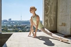 Ballerina posing at unfinished building. Delightful ballerina is posing on the concrete floor of the unfinished building on the cityscape background. She wears a Stock Photos