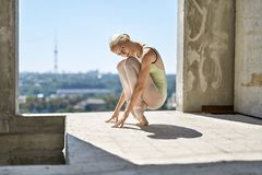 Ballerina posing at unfinished building. Gorgeous ballerina is posing on the concrete floor of the unfinished building on the cityscape background. She wears a Royalty Free Stock Photos