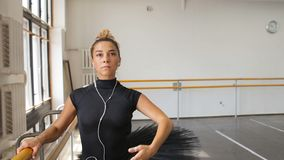 The ballerina practices in the big hall and listens to music on the smartphone.  stock video footage