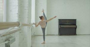 Ballerina practicing grand battement exercise. Graceful classic ballet dancer practicing grand battement exercise at barre during rehearsal in ballet studio stock footage