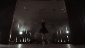 Ballerina is practicing her moves in dark studio. Young girl dancing with air white dress tutu, spinning around and. Smiling. Gracefulness and tenderness in stock footage