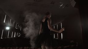 Ballerina is practicing her moves in dark studio. Young girl dancing with air white dress tutu, spinning around and. Smiling. Gracefulness and tenderness in stock video