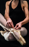 Ballerina preparing her ballet shoes Stock Image