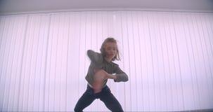 Ballerina professionista caucasica tenera che balla attivamente e che fila nello studio leggero sul fondo delle feritoie video d archivio