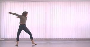 Ballerina professionista caucasica tenera che balla charmingly e che fila nella classe leggera sul fondo delle feritoie archivi video