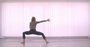 Ballerina professionista caucasica tenera che balla charmingly nello studio leggero sul fondo delle feritoie stock footage