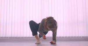 Ballerina professionista caucasica tenera che si scalda facendo gamba-spaccatura in studio leggero sul fondo delle feritoie stock footage