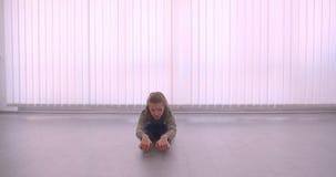 Ballerina professionista caucasica tenera che si scalda le sue gambe in studio leggero sul fondo delle feritoie archivi video