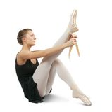 Ballerina puts on pointe Stock Photography